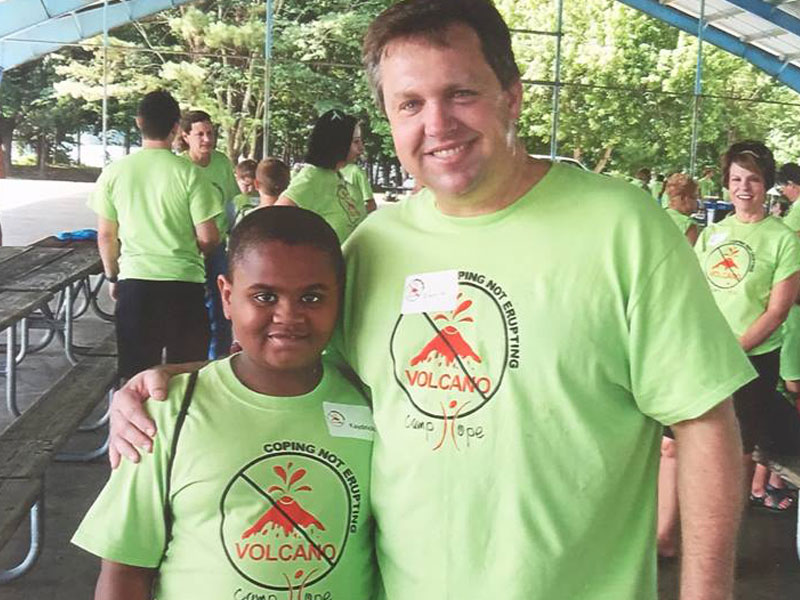 Stovall Marks Team Member with a Child at Camp Hope.